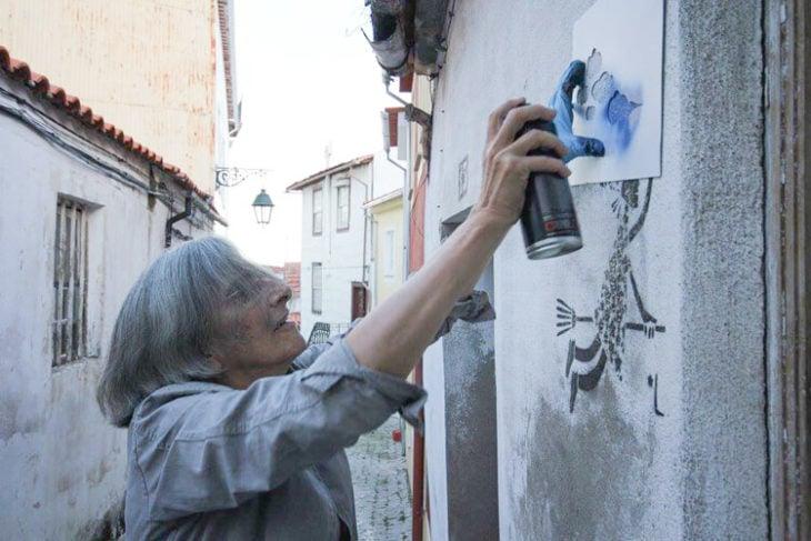 anciana hace graffiti en una pared