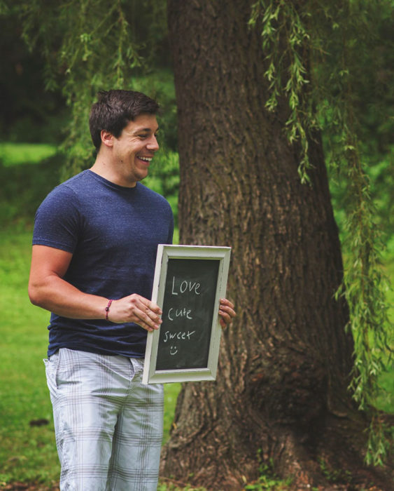 Hombre sonríe mientras sostiene un letrero que dice AMOR LINDO Y DULCE