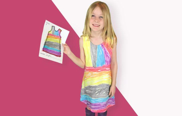 niña sosteniendo un dibujo de un vestido