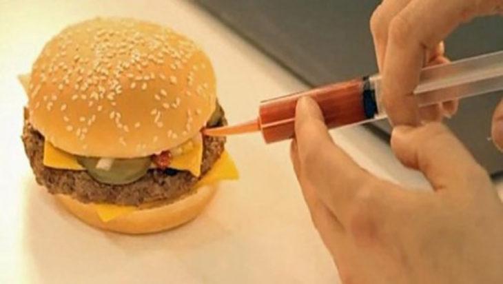 inyectando catsup a una hamburguesa