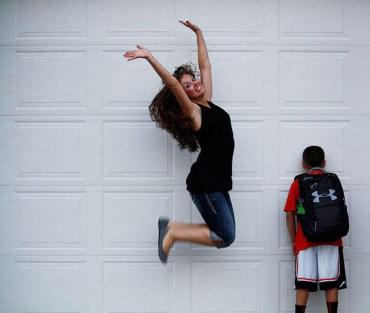 mujer saltando al lado de un niño