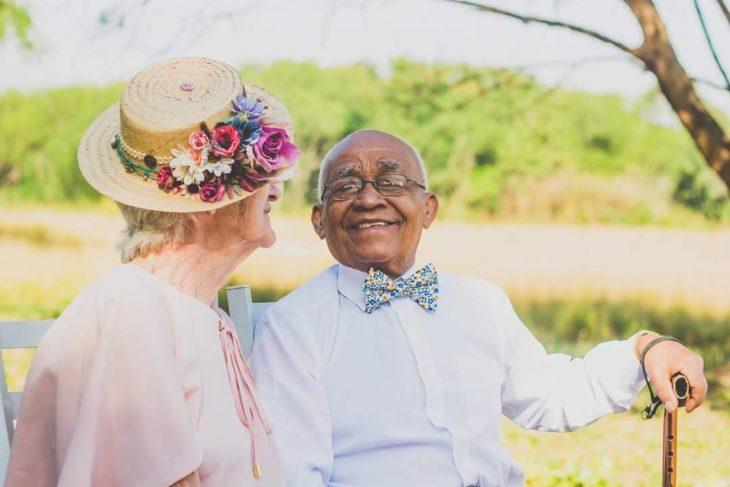 anciano sentado sonriendo a anciana que está a su lado