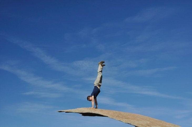 hombre parado sobre sus manos en una roca