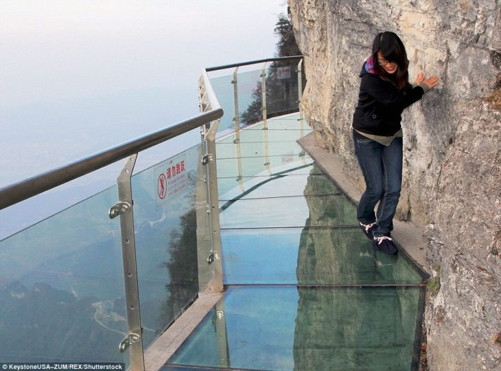 muchacha asustada arriba de un puente transparente