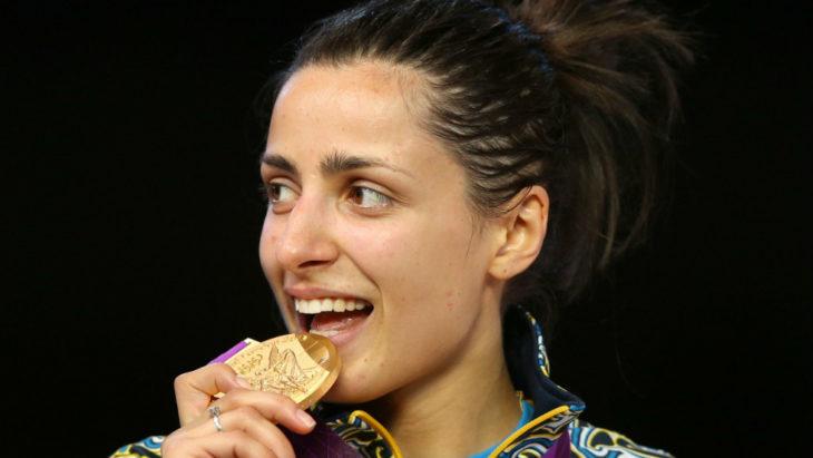 una atleta muerde medalla de oro