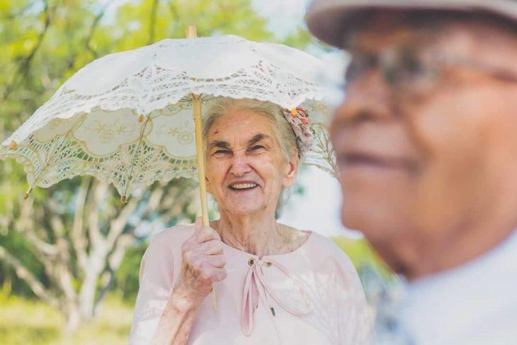 anciana con una sombrilla sonriendo detrás de un anciano