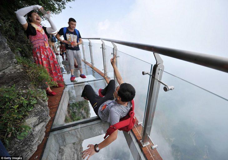 muchacho tomándose una foto en un puente transparente