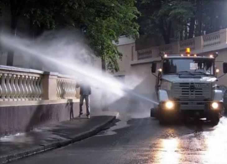 Hombre caminando lo llenan de agua un camión que riega las plantas