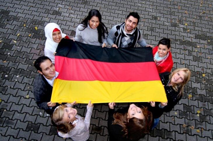 Estudiar en Alemania. Chicos sosteniendo una bandera de Alemania