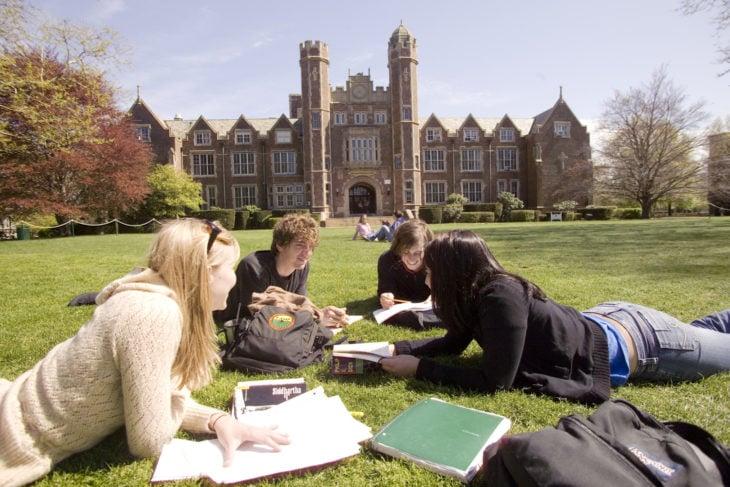 Estudiar en Estados Unidos. Chicos acostados en el cesped mientras estudian
