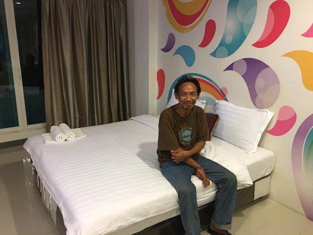 Waralop sonriendo mientras está sentado en su cama