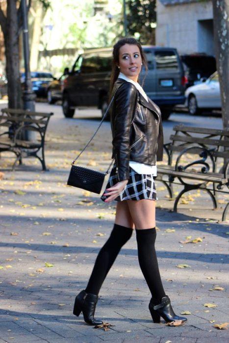 Foto de una chica con medias hasta la rodilla, zapatos cerrados, una bolsa chica, falta de cuadros cortita, y chamarra de cuero