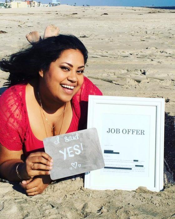 Benita Abraham acostada en la playa con una foto enmarcada que dice OFERTA DE EMPLEO y un letrero que dice DIJE QUE SÍ