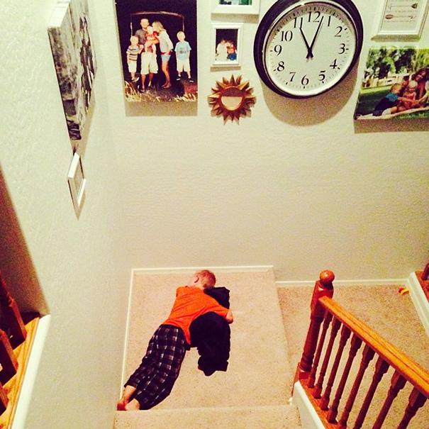 Niño dormido en las escaleras con su perro