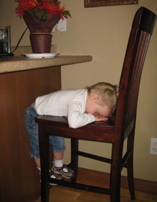 Niña dormida en la silla
