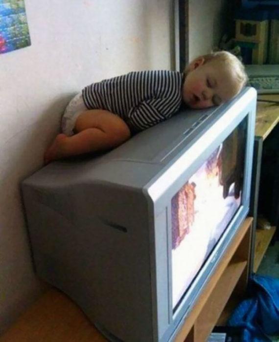 Niño dormido sobre televisión