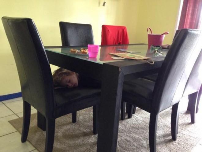 Niño dormido abajo del comedor