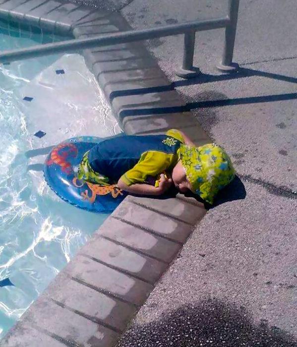 Niño dormido mitad cuerpo en la alberca y mitad en el piso