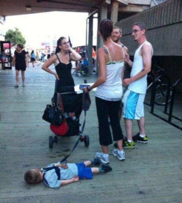 Niño dormido en la calle mientras su mama platica