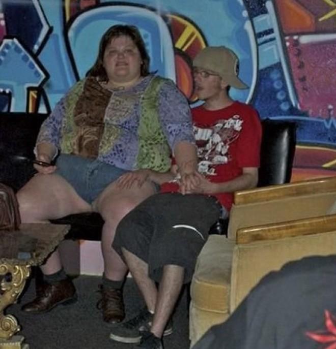Mujer con obesidad con un mini short con joven flaquito tocandole la pierna