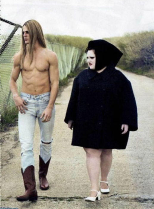 Hombre de cabello largo maquillado sin camisa y con un pantalón y unas botas vaqueras y mujer con un vestido negro y la cara pintada