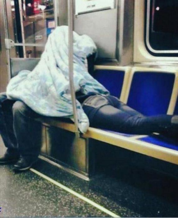 Hombre sentado y mujer acostada boca abajo en el metro tapados por una cobija