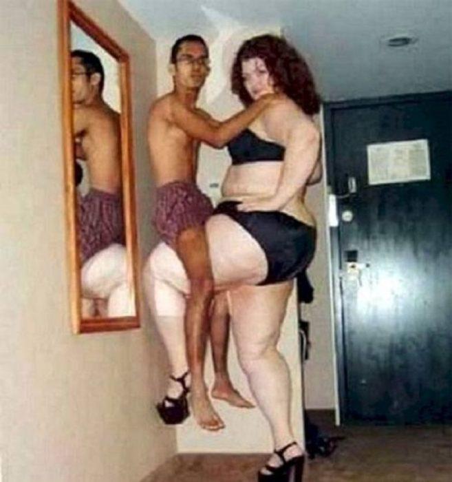 Pareja en ropa interior, mujer carga al hombre con su pierna, ella es muy alta y el es muy flaco y chiquito