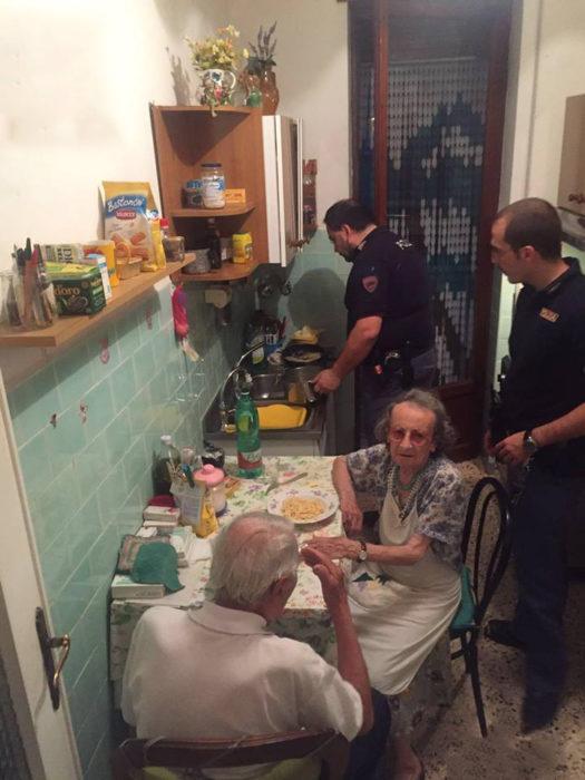 Dos policias en la cocina con una pareja de ancianos