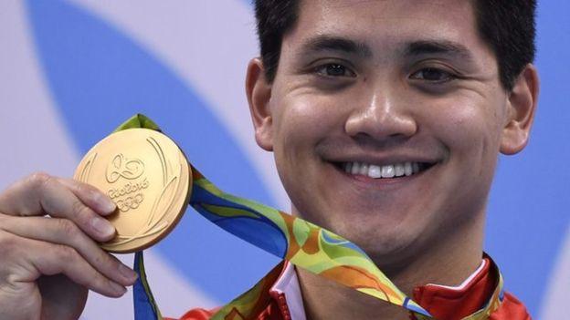 Joseph Schooling sosteniendo la medalla de oro de Rio 2016