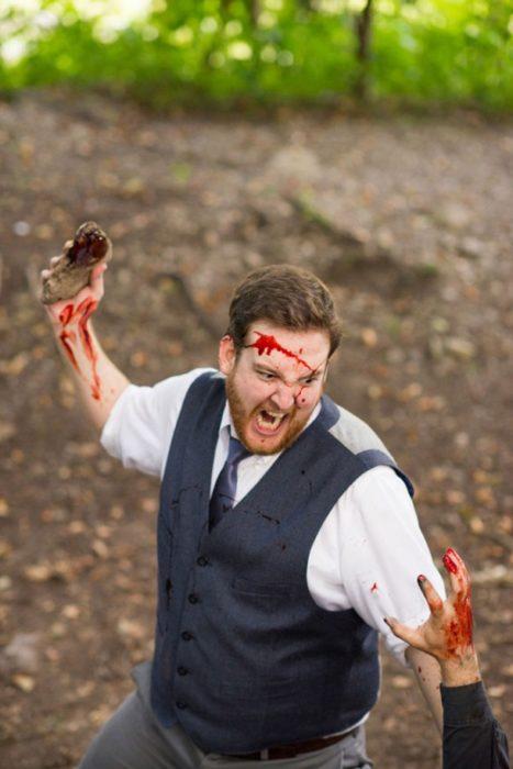 hombre manchado de sangre con una piedra en la mano