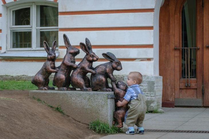 niño tratando de subir un conejo