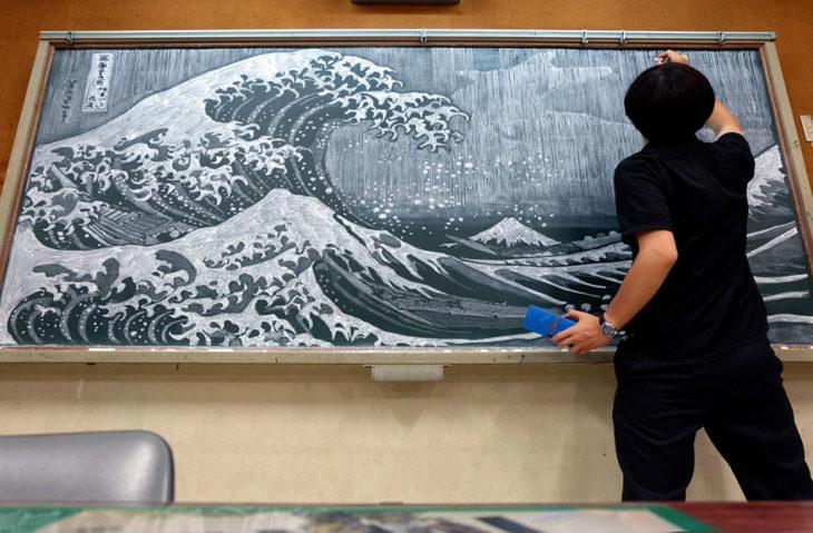 hombre pintando olas en pizarrón