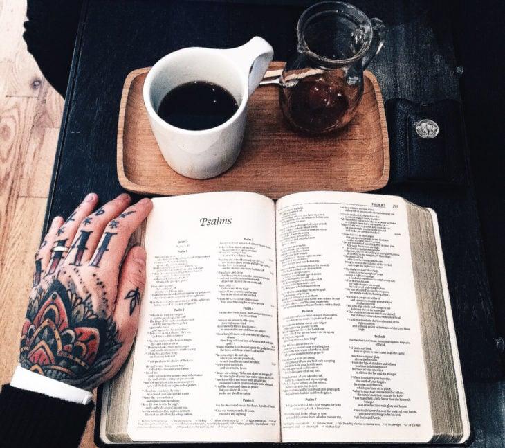 mano tatuada, libro y café