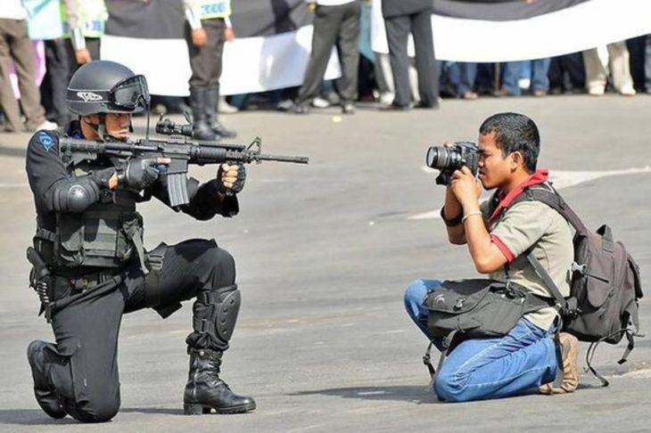 policía apuntando a un fotógrafo