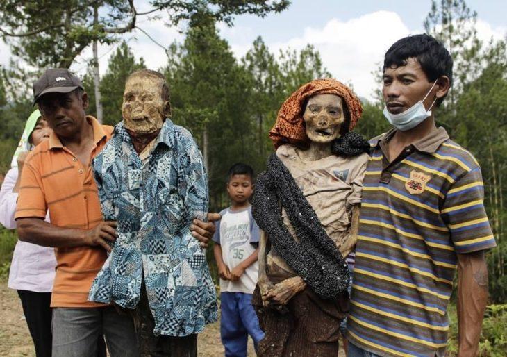 personas tomándose fotos con momias
