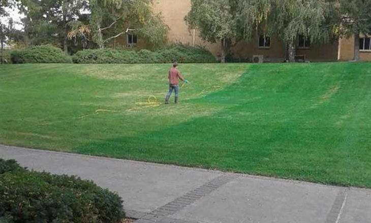 hombre pintando el pasto de color verde