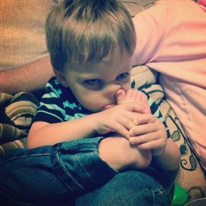 niño con un dedo del pie en la nariz