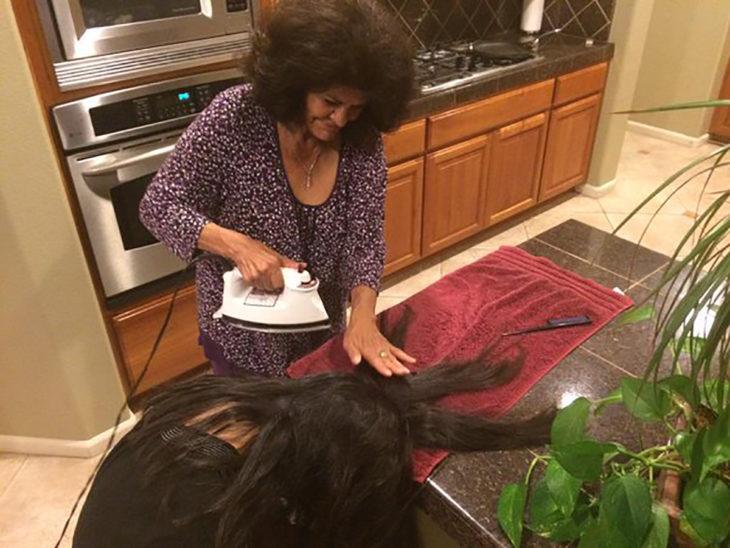 señora planchando el pelo a muchacha