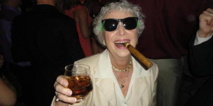 anciana con copa de licor y puro