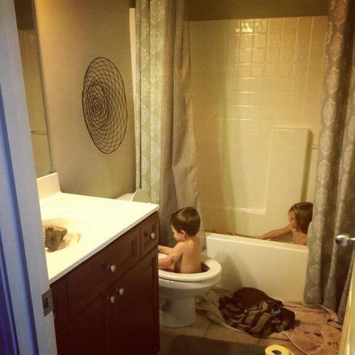 una niña bañándose en la bañera y niño bañándose en la taza de baño