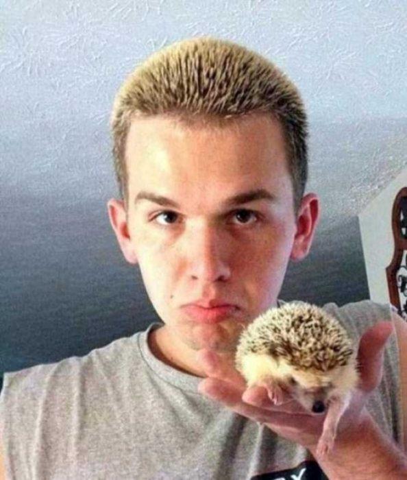 chico con el pelo de puercoespín tiene un puercoespín en la mano