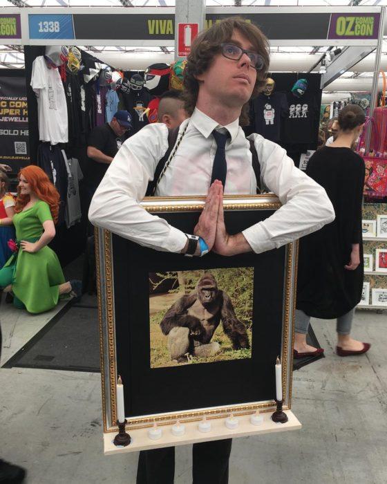 hombre con un cuadro de harambe el gorila
