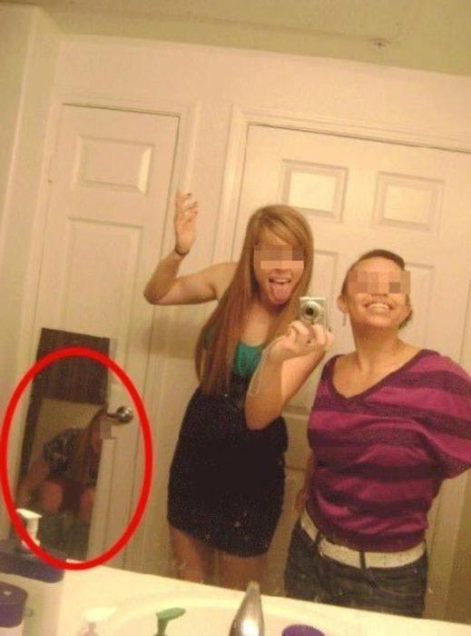 dos amigas tomándose foto en el baño mientras la tercera está en el inodoro