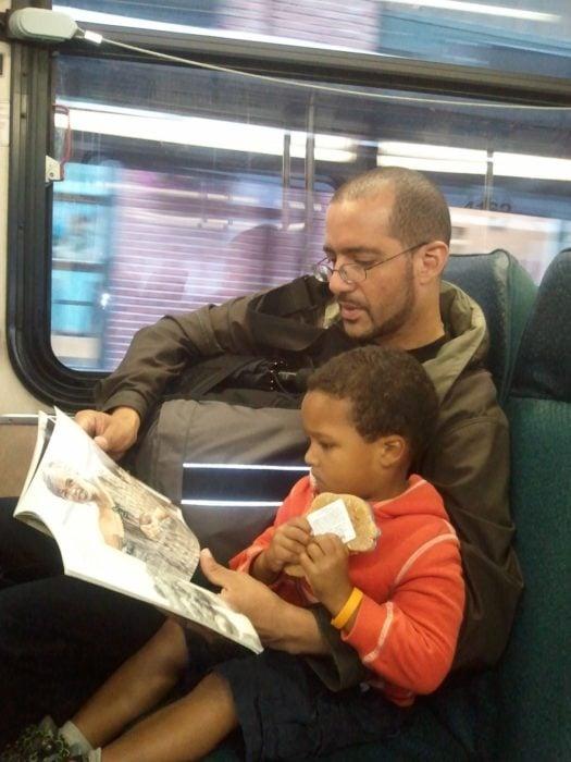 hombre leyendo un libro a un niño en un autobús