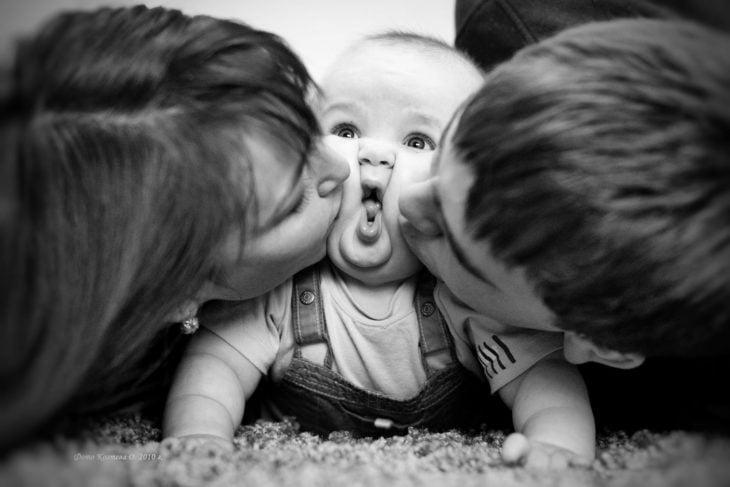 padres besando a su bebé