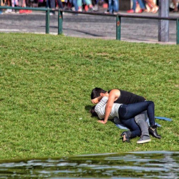 pareja besándose en el pasto