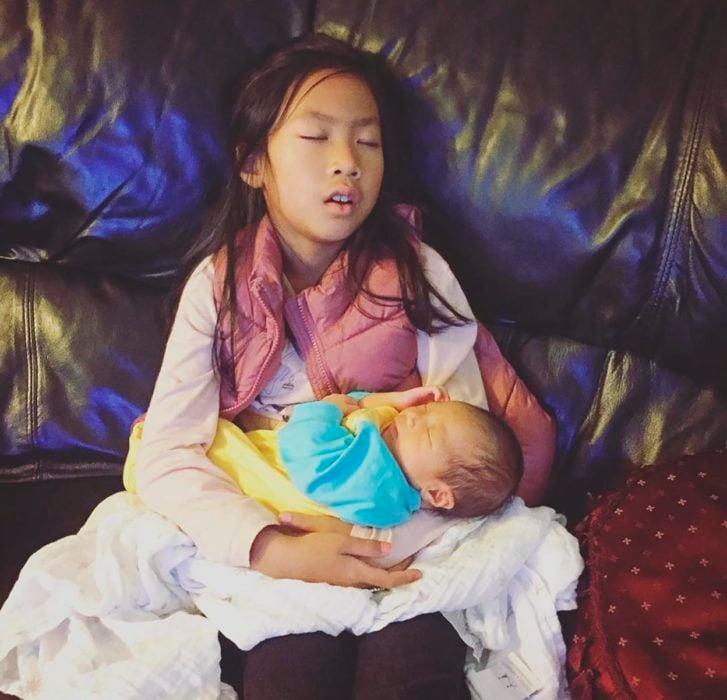 niña cargando un bebé