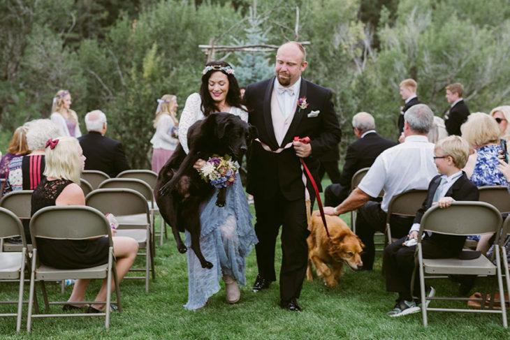 dos personas cargando un perro