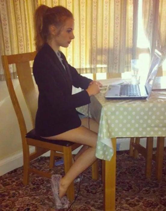 mujer sentada con una computadora, sin pantalones