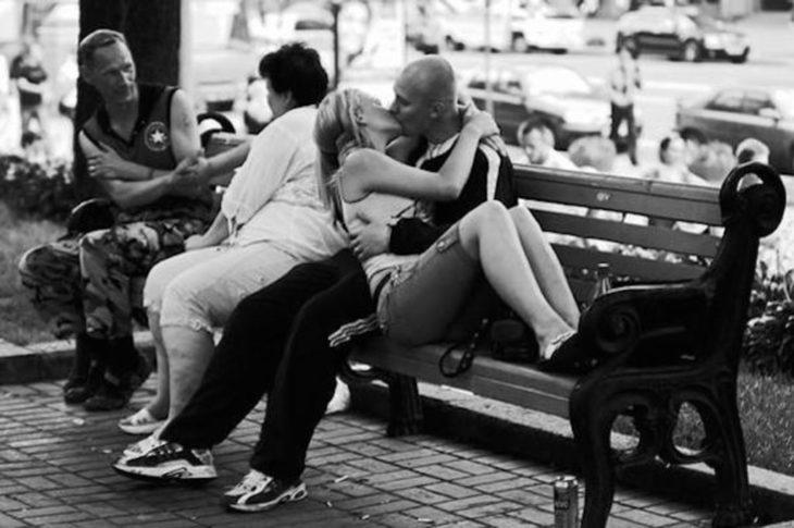 pareja besándose en una banca